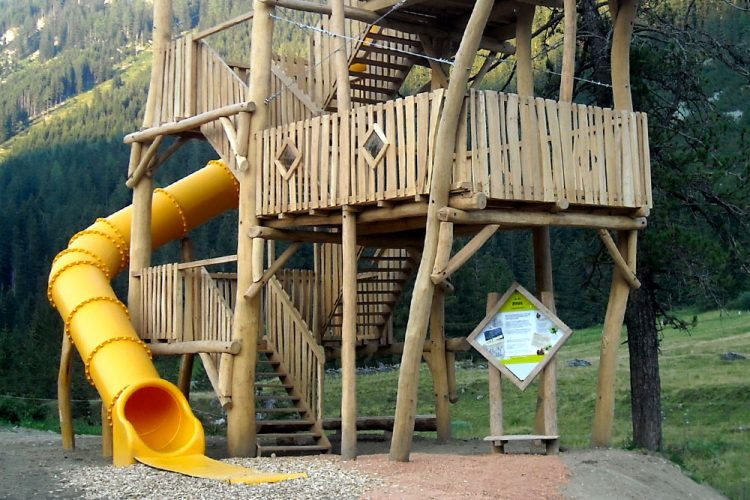 Ledon tube slide added onto an existing natural play structure